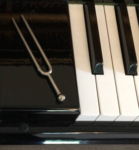 image of a piano tuning fork on a keyboard